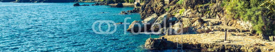 73774754 – Italy – Elba island panorama of rocky coastline beach with umbrella.