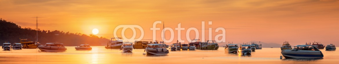 75708683 – United Arab Emirates – sunrise with colorful sky and boats on the beach