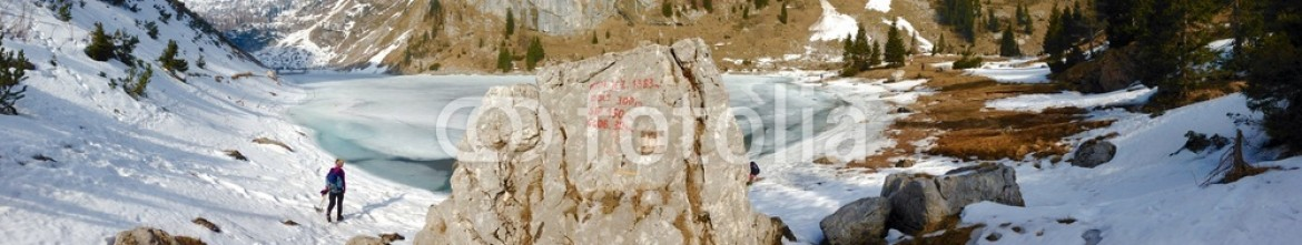 83549187 – Slovenia – Mountainous landscape and frozen lake with hiker on shore