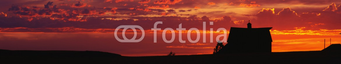 90028217 – United States of America – This is a farm at sunset. The farm house is silhouetted against an orange sky.