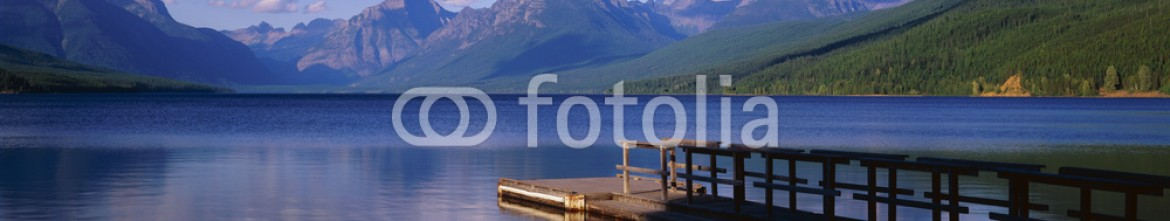 90028673 – United States of America – This is a boat dock at Lake McDonald. The blue water of the lake surrounds the dock with mountains in the background.