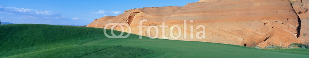 90029838 – United States of America – This is the Page Municipal Golf Course with a background hill made of sandstone rock. It shows a green golf course in the middle of a desert environment.