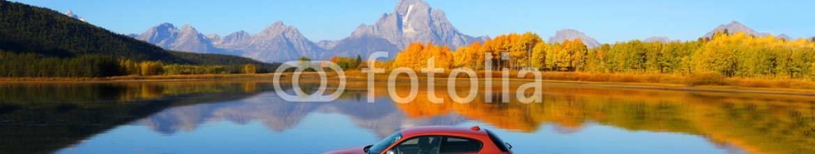 91072865 – Germany – Panorama of a red sports car driving on autumn road