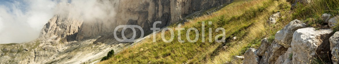 91325982 – Italy – view of meadow at the foot of mountain ridge