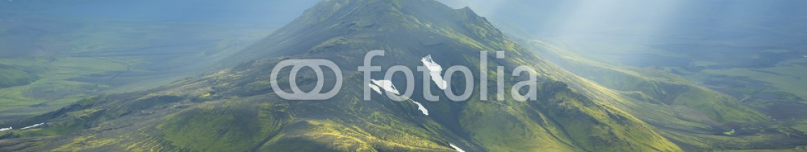 91618310 – Iceland – Sun breaking through the clouds on a mountain on the Laugavegur hiking trail on Iceland.