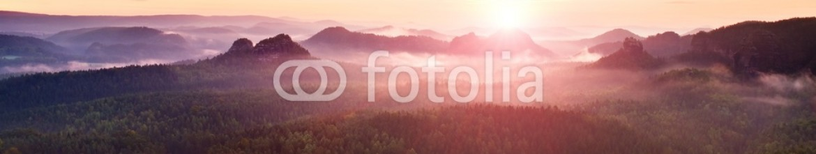 91953553 – Germany – View over sandstone cliff into deep misty valley in Saxony Switzerland. Sandstone peaks increased from heavy foggy background.
